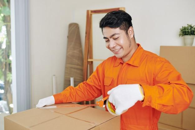 Glimlachende werknemer verzegelende dozen