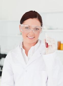 Glimlachende wetenschapper die de camera bekijkt terwijl het houden van een reageerbuis