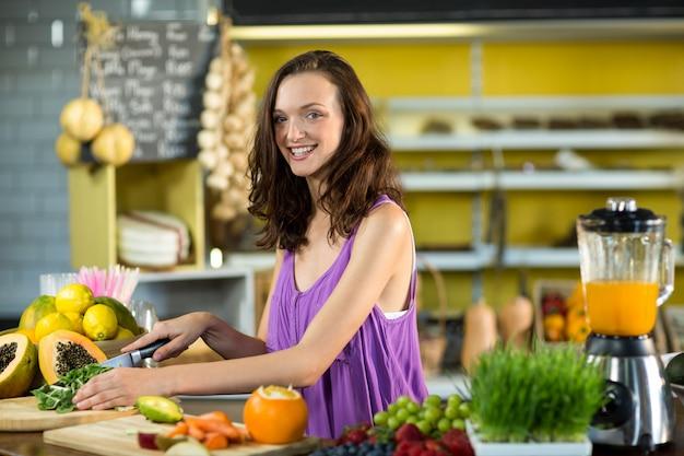 Glimlachende winkelbediende die bladgroente hakken aan balie