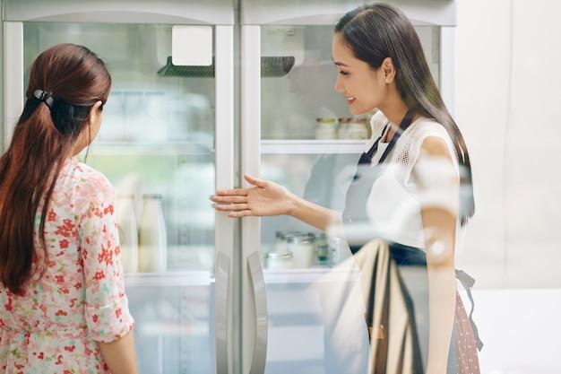 Glimlachende winkelbediende die klantenkoelkasten met lasctosevrije zuivelproducten en verse yoghurt toont