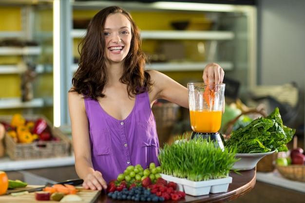 Glimlachende winkelbediende die papajasap voorbereidt