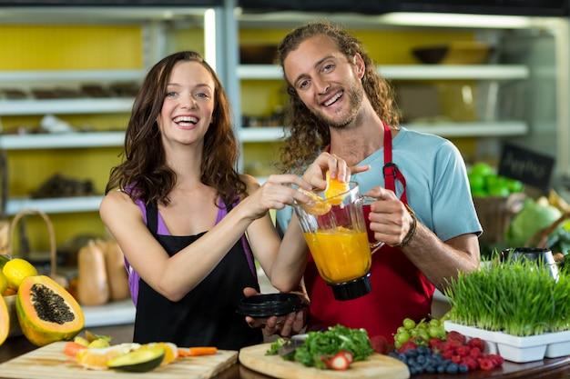 Glimlachende winkelbediende die sap bij gezondheid kruidenierswinkelwinkel voorbereidt