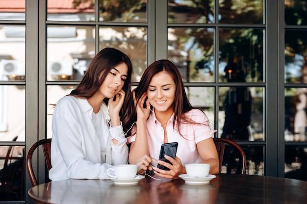 Glimlachende zakelijke dames luisteren naar belangrijke storingen in de hoofdtelefoon.
