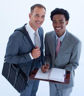 Glimlachende zakenlieden die in een bedrijfsagenda schrijven