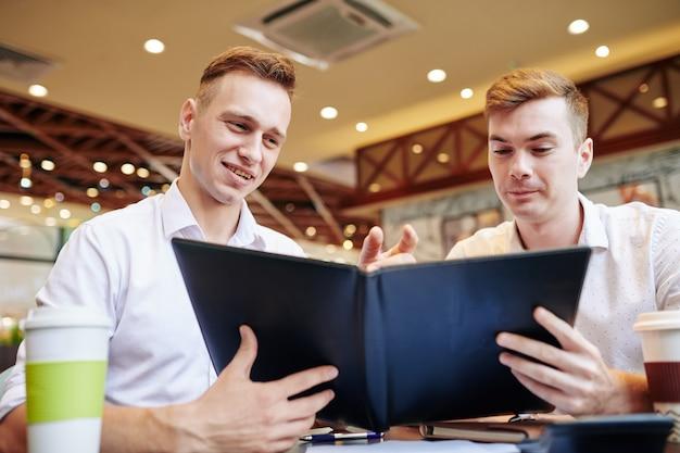 Glimlachende zakenlieden die menu lezen
