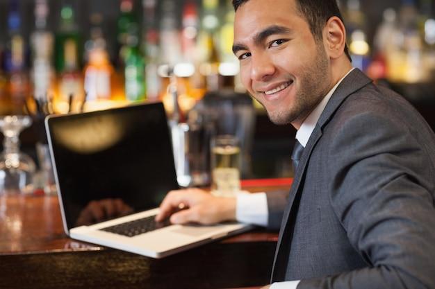 Glimlachende zakenman die aan zijn laptop werkt terwijl het hebben van een drank