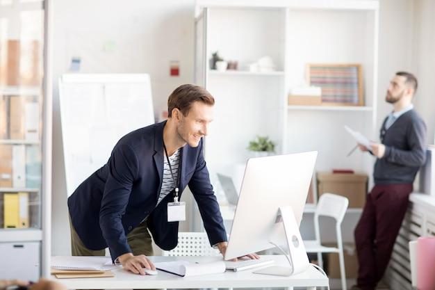 Glimlachende zakenman die computer met behulp van