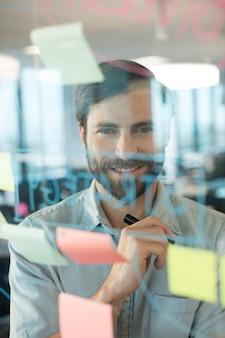 Glimlachende zakenman die door plannen kijkt die op glas worden geschreven