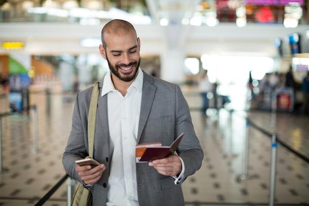 Glimlachende zakenman die een instapkaart houdt en zijn mobiele telefoon controleert