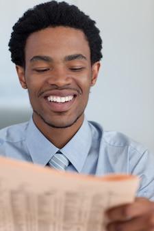 Glimlachende zakenman die een krant leest