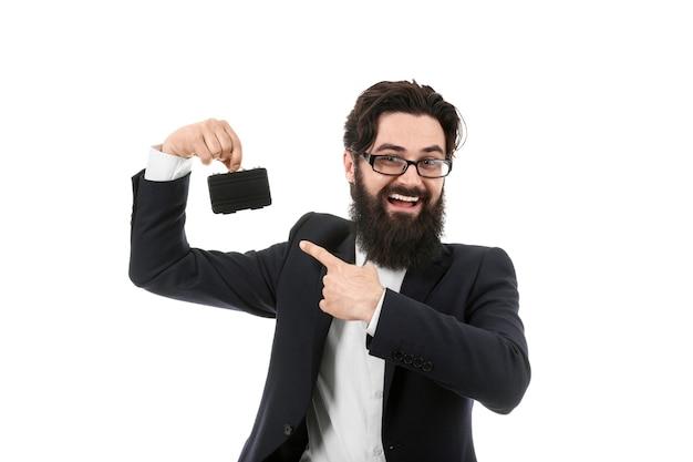 Glimlachende zakenman die een miniaktentas houdt, die op witte achtergrond, klein bedrijfsconcept wordt geïsoleerd