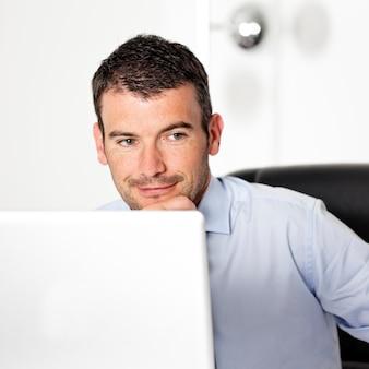 Glimlachende zakenman die in bureau met pen omhoog kijkt