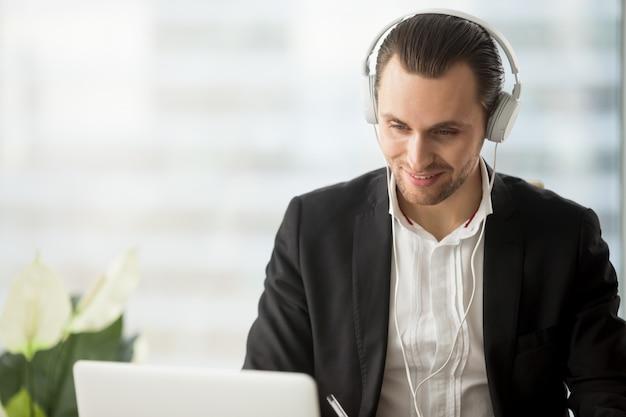 Glimlachende zakenman die in hoofdtelefoon het laptop scherm bekijkt.