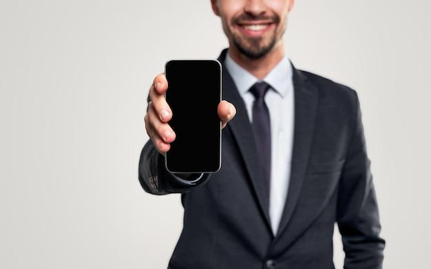 Glimlachende zakenman die in kostuum smartphone toont