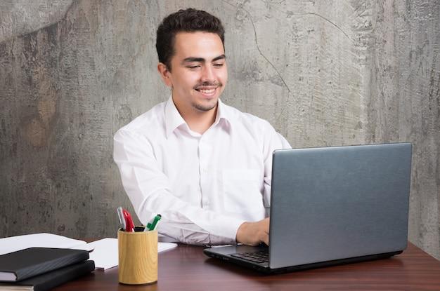 Glimlachende zakenman die laptop onderzoekt en aan het bureau zit. hoge kwaliteit foto
