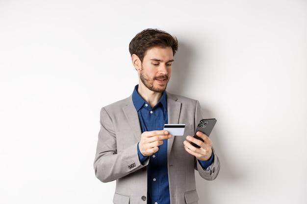 Glimlachende zakenman die met creditcard op smartphone betaalt
