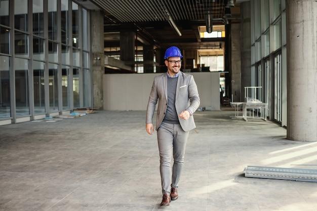 Glimlachende zakenman die met helm op hoofd door bouwplaats van zijn gebouw loopt.