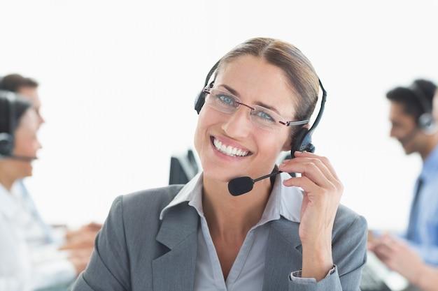 Glimlachende zakenman die met hoofdtelefoons camera bekijken