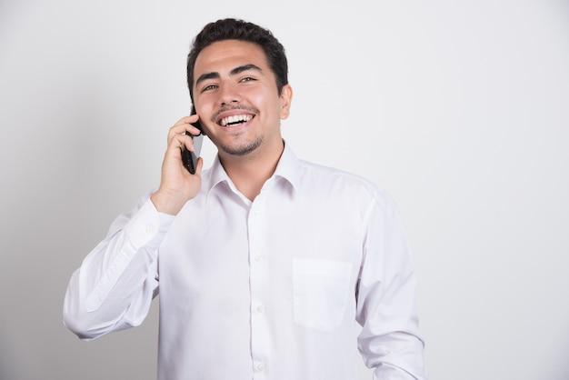 Glimlachende zakenman die met telefoon op witte achtergrond spreekt.