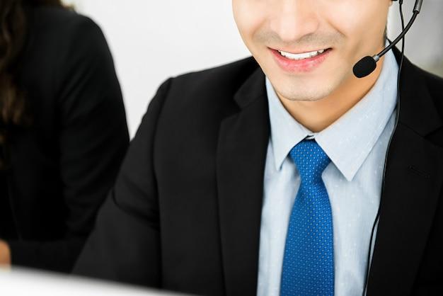 Glimlachende zakenman die microfoonhoofdtelefoon draagt die in call centre werkt