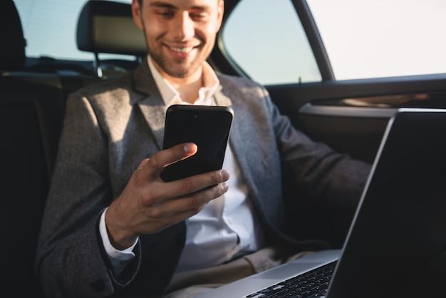 Glimlachende zakenman die mobiele telefoon houdt
