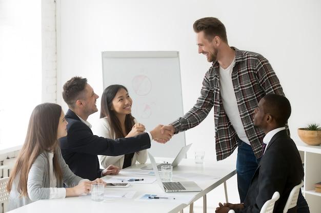 Glimlachende zakenman die nieuwe partner welkom heten bij groepsvergadering met handdruk