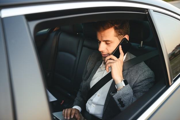 Glimlachende zakenman die op mobiele telefoon spreekt