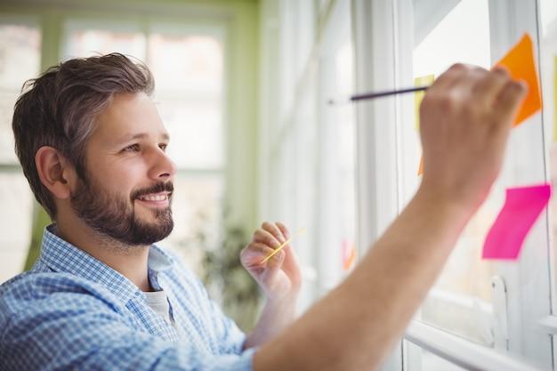 Glimlachende zakenman die op zelfklevende nota's op kantoor schrijven