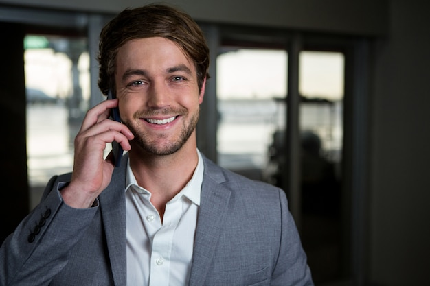 Glimlachende zakenman die op zijn mobiele telefoon in de luchthaventerminal spreekt