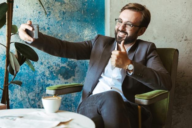 Glimlachende zakenman die pak draagt dat een selfie neemt terwijl hij in het koffie zit en koffie drinkt