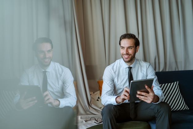 Glimlachende zakenman die tablet gebruikt.