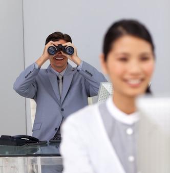 Glimlachende zakenman die verrekijkers met behulp van