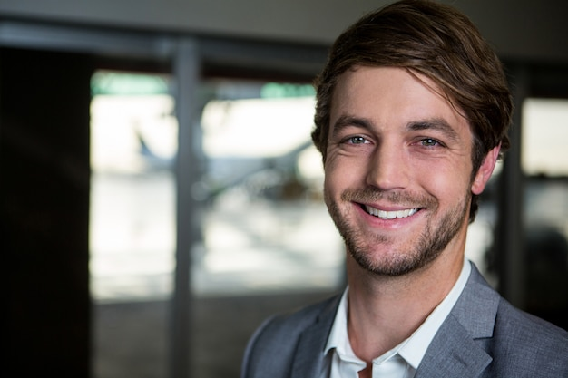 Glimlachende zakenman die zich op luchthaven bevindt