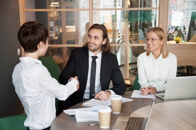 Glimlachende zakenman en onderneemster het schudden handen op de onderhandelingen van de groepsvergadering