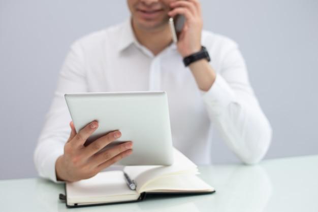 Glimlachende zakenman gebruikend digitale tablet en sprekend op telefoon