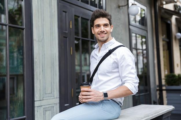 Glimlachende zakenman gekleed in overhemd buiten zitten