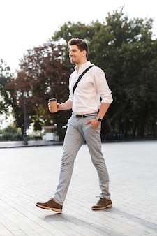 Glimlachende zakenman gekleed in overhemd lopen buiten