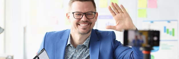 Glimlachende zakenman houdt financieel klembord in zijn handen en neemt video op op camera-afstandsbediening