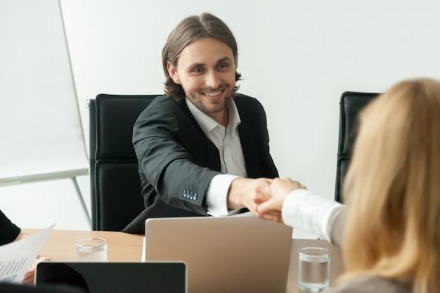 Glimlachende zakenman in kostuum handenschudden vrouwelijke partner op groepsvergadering