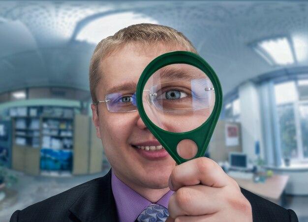Glimlachende zakenman kijkt naar je door vergrootglas