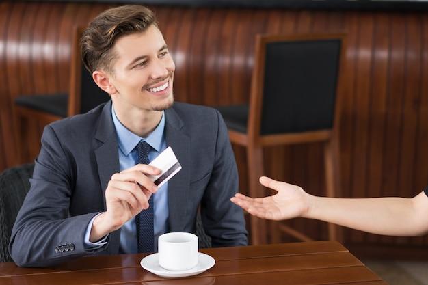 Glimlachende zakenman met creditcard betaalt in cafe