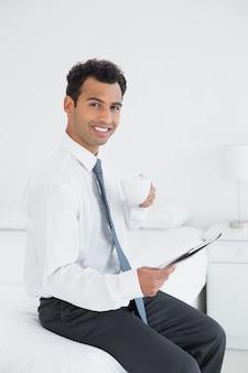 Glimlachende zakenman met de krant van de koplezing bij hotelruimte