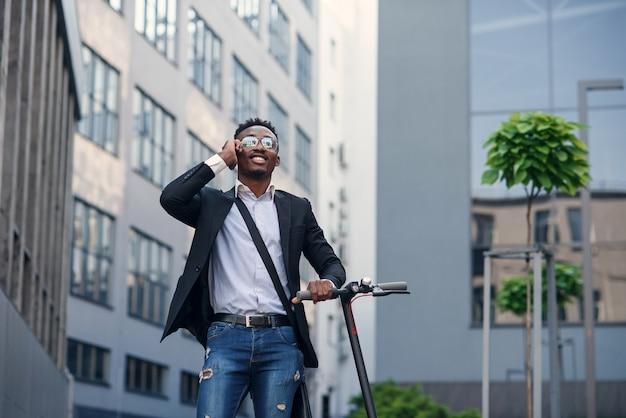 Glimlachende zakenman met elektrische autoped dichtbij modern bedrijfsgebouw