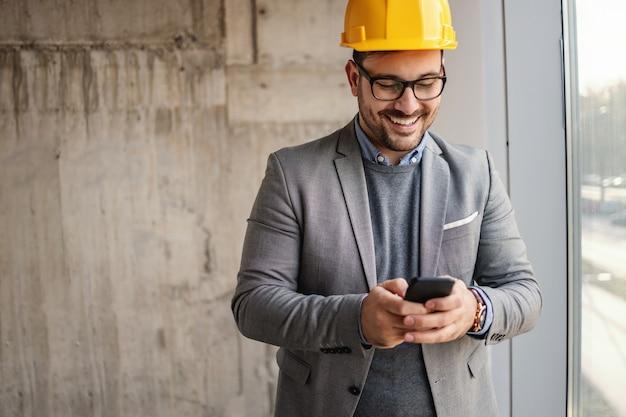 Glimlachende zakenman met helm op hoofd die zich naast een venster in gebouw in bouwproces bevinden en telefoon gebruiken.