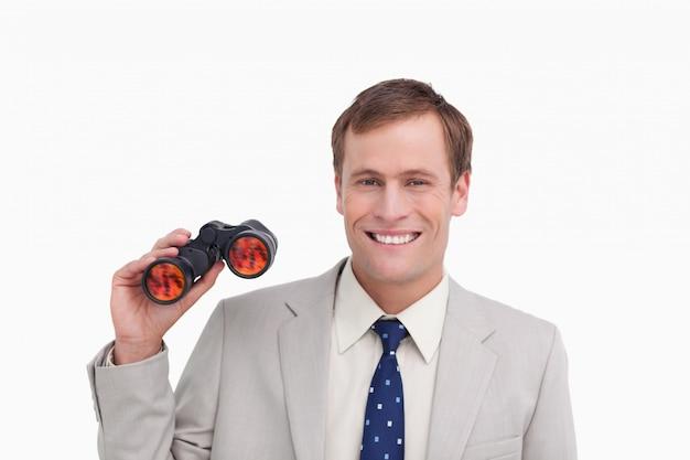 Glimlachende zakenman met kijker glazen