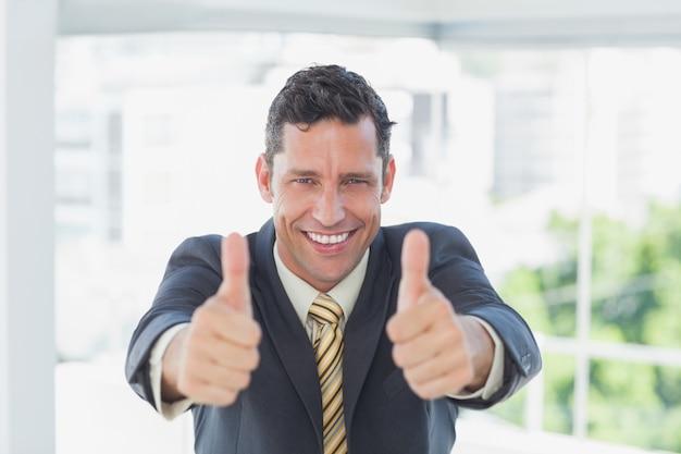 Glimlachende zakenman met omhoog duimen