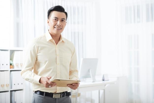 Glimlachende zakenman met tablet in bureau