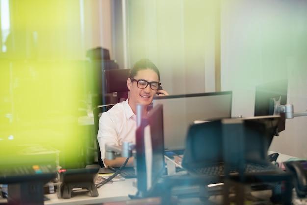 Glimlachende zakenman praten over de telefoon op kantoor