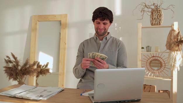 Glimlachende zakenman telt geld zittend in het kantoor