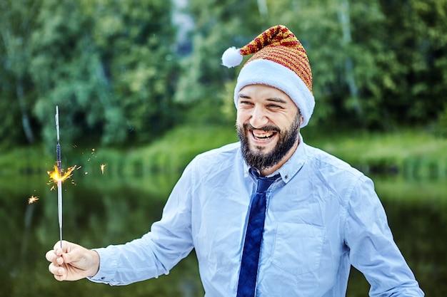 Glimlachende zakenman viert kerstmis op groene bosachtergrond.